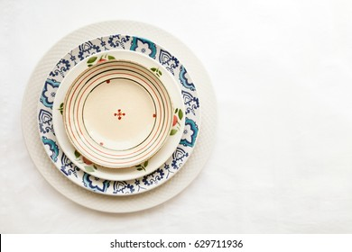 Stack of empty ceramic plates isolated on white background with copy space. Cheerful colorful dishes decorated with floral pattern. Beautiful vintage crockery top view