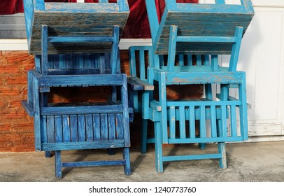 Stack of Empty Vintage Blue Wooden Chairs In Front of The Traditional Coffee Shop.