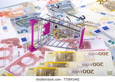 Stack of Euro banknotes with shopping cart in money consuming concept, on full background.