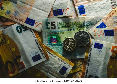 Stack of euro bills cornering a pound note by the brexit.