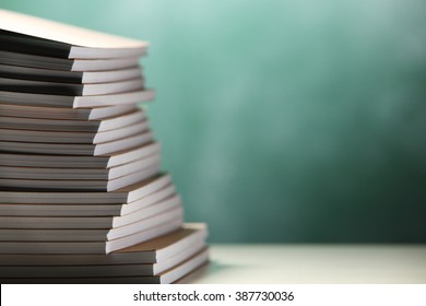 stack of exercise book in front of chalkboard