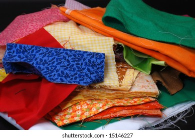 Stack of fabric swatches on black background.