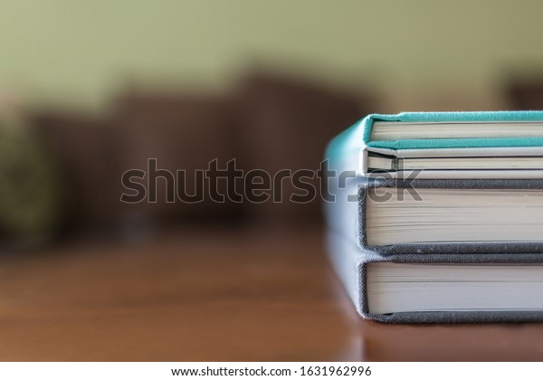 Stack of family photo albums on a wooden coffee table
