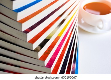Stack of fiction books with a cup of coffee on white background.