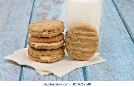 A stack of filled peanut butter and oatmeal cookies with one leaning on a glass of milk.  Blue rustic table.  Copy space.
