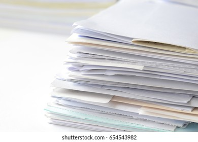 Stack of financial documents on white table with high key tone.