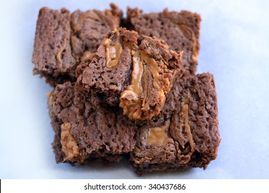 stack of five brownies with peanut butter swirl on white parchment paper background