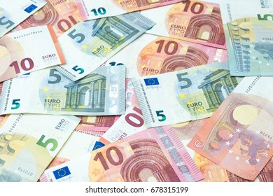 Stack of five and ten euro banknotes as money and currency background.