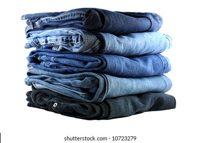 stack of five various shades of blue jeans on a white background