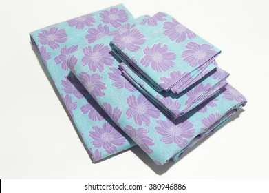 Stack of floral patterned sheets on white background