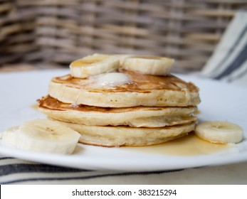 Stack of fluffy pancakes with butter fresh bananas and maple syrup on white plate