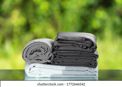 Stack of folded bedding. Monochrome gray gradient plaid towel bedsheet textile set on blurred foliage background.
