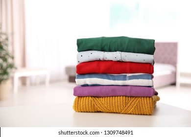 Stack of folded bright clothes on table against blurred background. Space for text