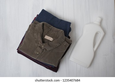 Stack of folded clothes and detergent bottle. Top view