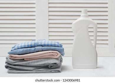 Stack of folded clothes and detergent bottle. White background
