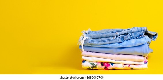 Stack folded colorful clothing summer on yellow background