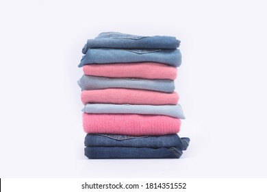 Stack folded colorful sweater with blue jeans clothing on white background