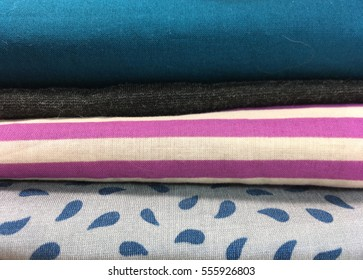 A stack of folded fabric in solids, dots and stripes