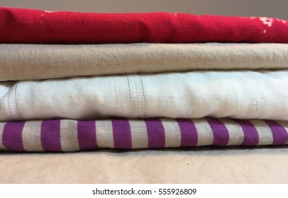 A stack of folded fabric in solids and stripes. Purple, red, white, red and taupe.