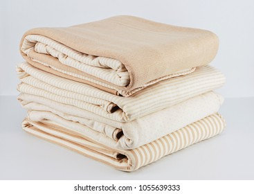 Stack of folded up natural beige cotton blanket for newborn on white background