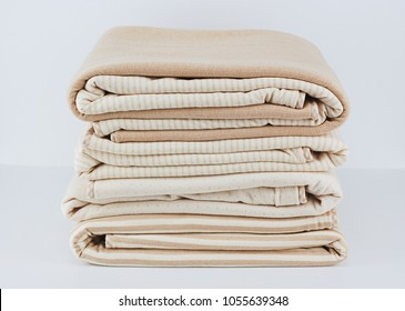 Stack of folded up natural cotton blanket for newborn on white background
