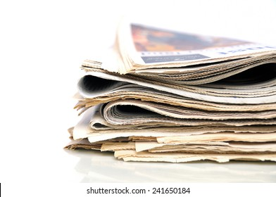 Stack of folded newspapers on white background