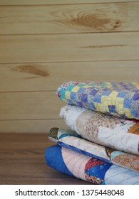 Stack of Folded Quilts on a Table