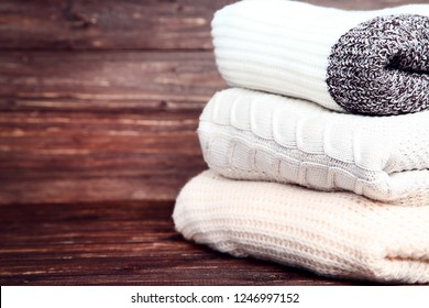 Stack of folded sweaters on brown wooden background