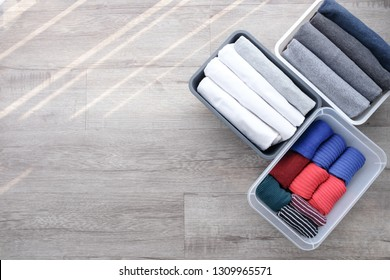 Stack of folded t shirt black gray white color and folded bright colorful socks in plastic baskets on wooden floor background in natural light with copy space. Room cleaning and tidying up concept.