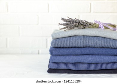 Stack of folded warm knitted men's sweaters in blue and a bunch of dried lavender on white background with copy space, care of clothes aroma and protection from moths concept. Horizontal. Close-up.