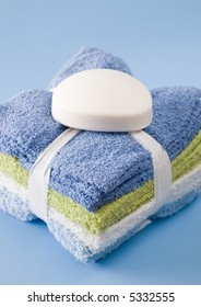 Stack of folded washcloths isolated on blue with bar of soap on top.
