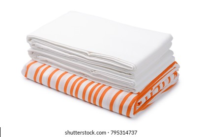 Stack of folded white and color bedding sheets isolated on white