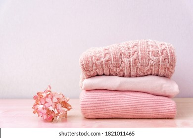 Stack of folded wool knitted sweaters or pullovers in pink pastel colors on table with flower hydrangea. Close up of warm cozy comfortable monochrome clothes for autumn winter season. - Shutterstock ID 1821011465