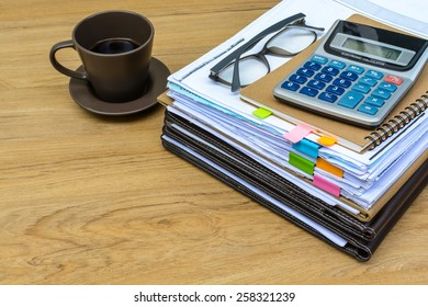 stack of folders and documents on office desk with coffee