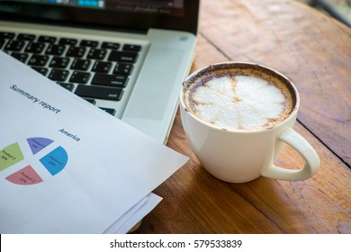 Stack of folders and documents on office desk with coffee and laptop