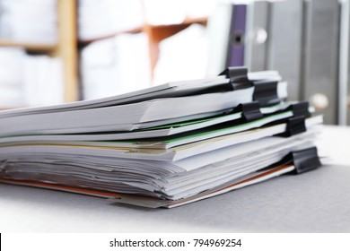 Stack of folders with documents on table in archive