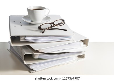 stack of folders, glasses and a cup of coffee on a desk, isolated on a white background, business and finance concept, copy space, selected focus