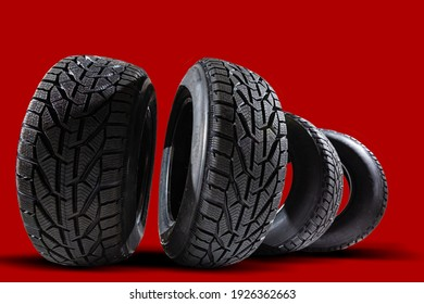 Stack of four new red tyres for winter car on blue background