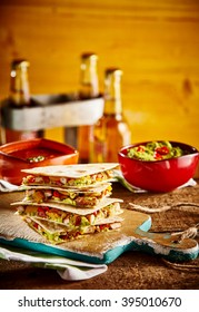 Stack of four quesadilla wedges on wooden cutting board next to guacamole bowl and beer bottles in background