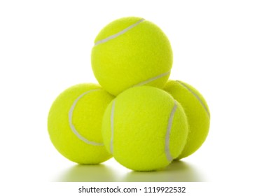 Stack of four vibrant yellow tennis balls isolated on white background