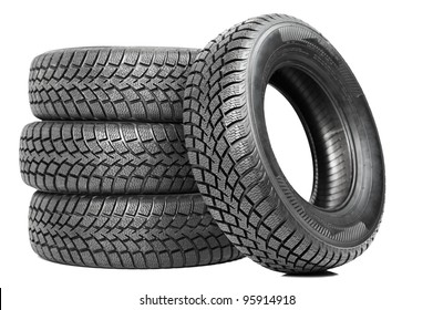 Stack of four wheel new black tyres for winter car driving isolated on white background