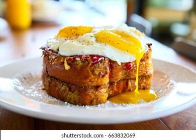 Stack of French Toast with Two Fried Eggs and Runny Yellow Yolk