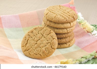 A stack of fresh baked peanut butter cookies on a pastel spring cloth napkin, horizontal with copy space, horizontal