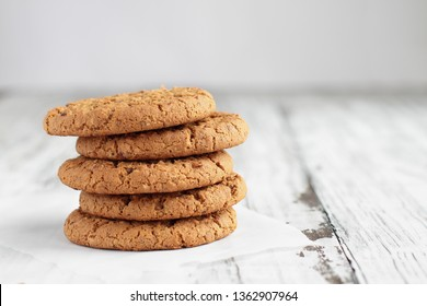 Stack of fresh homemade oatmeal cookies with a bottle of milk on a white table against a white background..