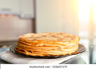 Stack of fresh pancakes on the kitchen table. Against the background of window with sunlight.
