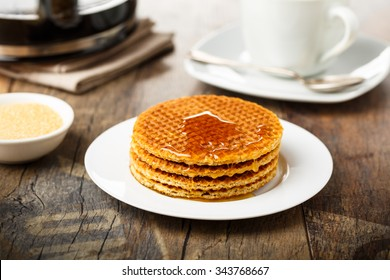 Stack of fresh Stroopwafels with honey and coffee.
