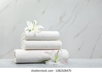 Stack of fresh towels with flowers on grey table against light background. Space for text
