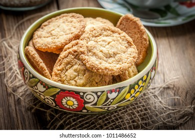 Stack of freshly baked oat biscuits in a bowl standing on a wooden table.