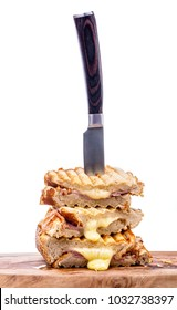 Stack of freshly cooked cheese and ham toasted sandwiches on a wooden serving board with a knife over a white background