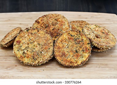 A stack of fried eggplant slices on a cutting board ready to be made into eggplant parmesan or eaten as is.